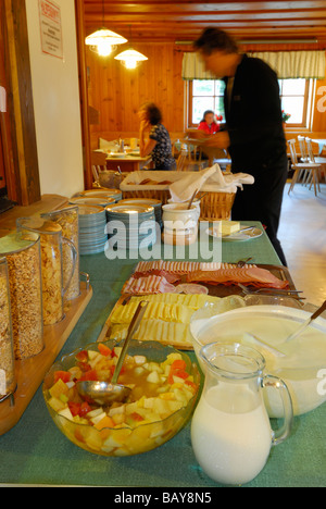 breakfast buffet with cereal and cold cuts, guests at tables out of focus in background, hut Franz-Senn-Huette, - Stock Photo