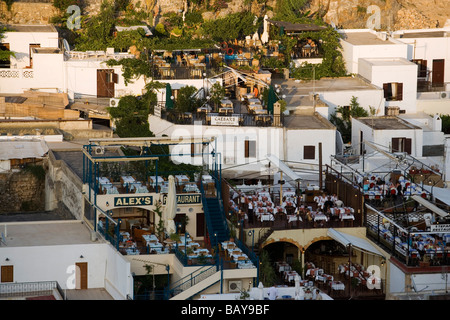 View over town in the evening, people sitting on terraces of restaurants, Lindos, Rhodes, Greece - Stock Photo