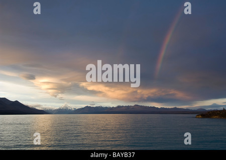 Clouds and rainbow over Mt Cook and Lake Pukaki South Island New Zealand - Stock Photo