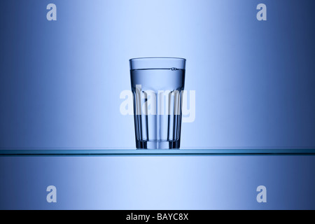 Glass of drinking water on blue background - Stock Photo