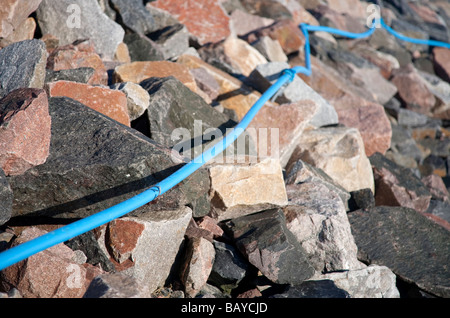 Surface mounted blue electrical cable on rocky terrain - Stock Photo