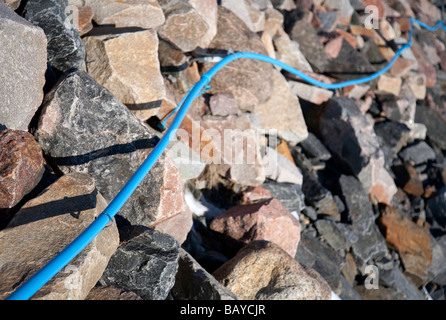 Surface mounted blue cable on rocky terrain - Stock Photo