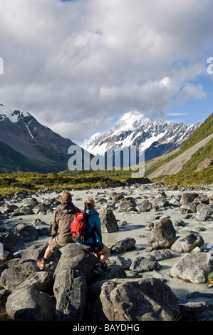 Couple admiring view of Mount Cook Hooker Valley trail Mt Cook Aoraki National Park South Island New Zealand - Stock Photo