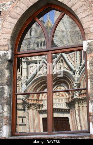 Duomo Santa Maria Assunta reflected in a window, Siena, Tuscany, Italy - Stock Photo