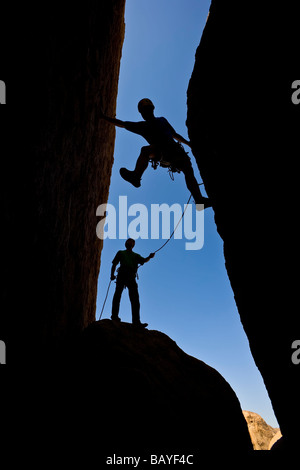 A team of rock climbers are silhouetted as they work their way up a chimney - Stock Photo