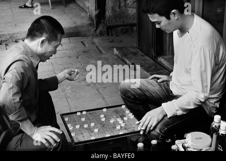 Two men play xiangqi on the streets of the Old Quarter, Hanoi, Socialist Republic of Vietnam. - Stock Photo