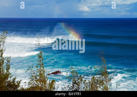 A rainbow forms off the spin drift from a large wave on Maui's North Shore, Hawaii. - Stock Photo