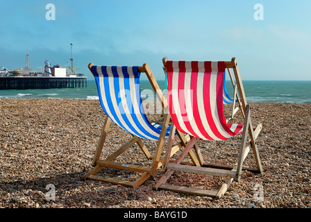 Two deckchairs on beach with Brighton Pier in background - Stock Photo