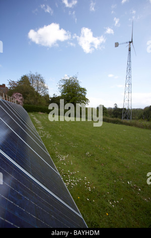 sun shining down on an array of blue tinted polycrystalline silicon photovoltaic solar panels and medium sized wind - Stock Photo