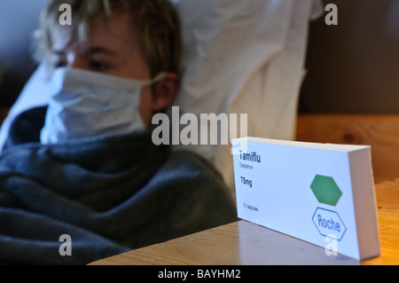 Teenage boy lying in bed wearing a mask with a box of Tamiflu sitting on his bedside table - Stock Photo