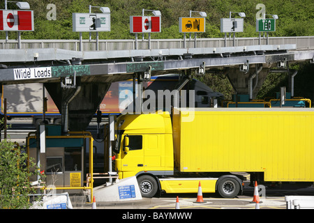 Yellow lorry paying at the toll plaza on the English side of the Severn Bridge road crossing, over the River Severn - Stock Photo