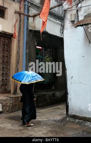 Woman with an umbrella during a rainshower in Stone Town Zanzibar - Stock Photo
