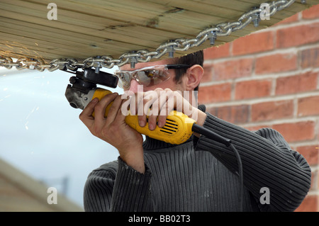 Young man wearing protective eye gear using small angle grinder on chain-link bridge. - Stock Photo
