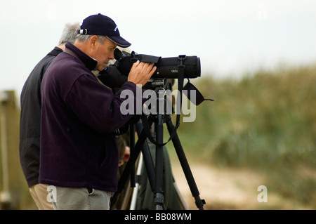 Birdwatchers using tripod-mounted telescopes on the beach at Titchwell bird reserve, North Norfolk, England - Stock Photo