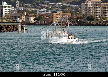 Fishing trawler passing through a breakwater on its way to the ocean for an evening of prawn fishing - Stock Photo