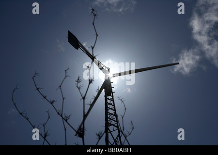 sun shining down on a medium sized wind turbine in county tyrone northern ireland - Stock Photo