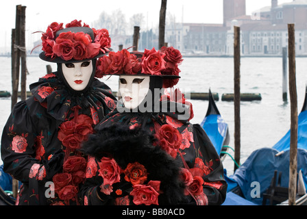 Couple in Venetian carnival disguise on San Marco wharf with gondolas on background - Stock Photo