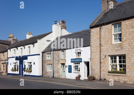 Terraced houses and The Blue Bell Inn on Hill Street in small historic town of Corbridge Northumberland England - Stock Photo