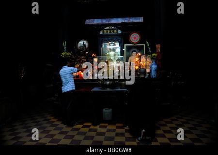 A man lights candles, a monk kneels in prayer. Emperor Jade Pagoda (Chua Ngoc Hoang or Phuoc Hai Tui), Ho Chi Minh - Stock Photo
