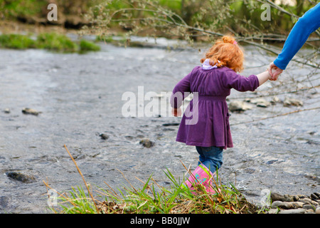 Little girl paddling in the river with red curly hair. - Stock Photo