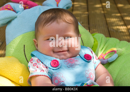 Horizontal close up portrait of a six month old baby girl shrugging her shoulders laughing in the garden on a sunny - Stock Photo