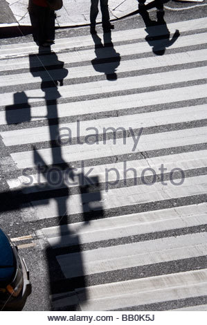 shadows of two people waiting to cross the road - Stock Photo