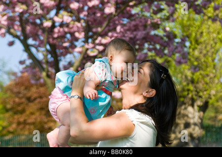 Horizontal close up portrait of a young mum playing with her baby daughter by lifting her up in the air outside - Stock Photo