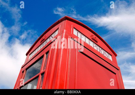 An iconic British telephone box contrasted against a blue sky and white clouds - Stock Photo