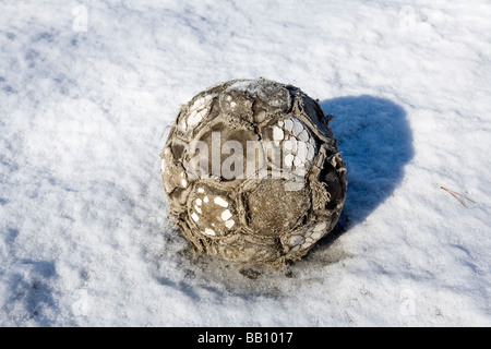 worn-out soccer ball on snow - Stock Photo