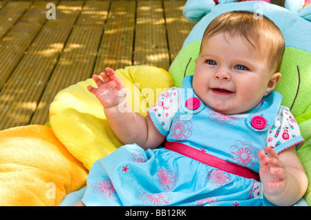 Horizontal close up portrait of a cute six month old baby girl sitting on a colourful cushion in the garden on a - Stock Photo