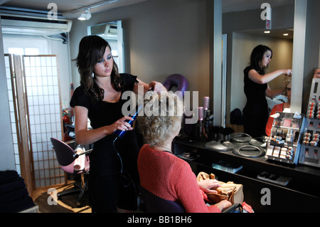 Hairdresser styling blonde womans hair with curling tongs - Stock Photo