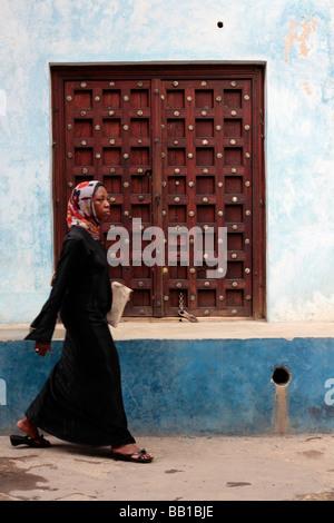 Woman in traditional costume walking past a window in Stone Town Zanzibar - Stock Photo