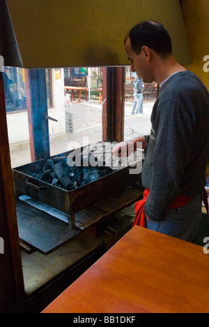 Man lighting up skara barbecue grill in a restaurant in Carsija district of Skopje Macedonia Europe - Stock Photo
