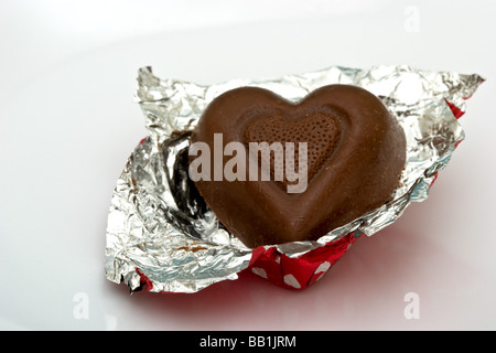 Single heart shaped chocolate candy in aluminum foil wrapping - Stock Photo