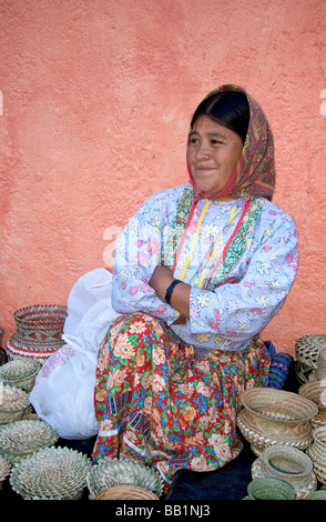 Tarahumara native Indian woman sits with woven baskets that she makes and sells to tourists Divisadero, Copper Canyon, - Stock Photo