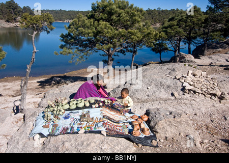 Tarahumara native Indian girl and small boy with crafts for sale by the banks of Lake Arareko near the town of Creel - Stock Photo