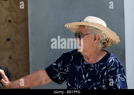 Elderly woman in traditional straw hat Saint Louis Festival Corossol St Barts - Stock Photo
