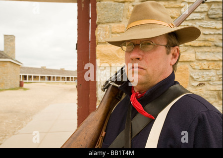 MAN IN PERIOD MILITARY UNIFORM AND RIFLE AT FORT SNELLING - Stock Photo