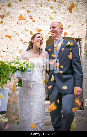 Newlywed couple with thrown flower petals after service - Stock Photo