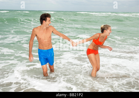Couple holding hands and walking in water on the beach - Stock Photo