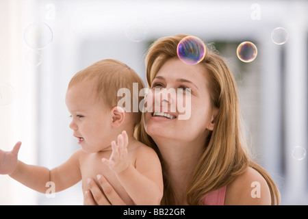 Woman and her baby trying to catch soap bubbles - Stock Photo