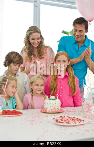 Girl celebrating her birthday with her parents and friends - Stock Photo