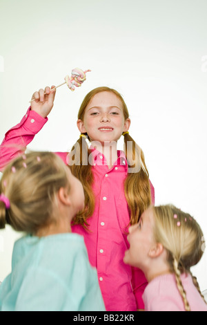 Girl holding a lollipop with her two friends standing beside her - Stock Photo