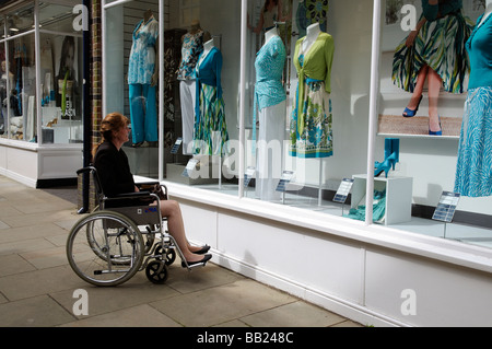 Woman seated in her wheelchair window shopping outside a ladies fashion store - Stock Photo