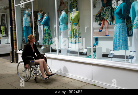 Female wheelchair user window shopping - Stock Photo