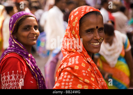 Two colourfully dressed women stand together in a market in the old city of Ahmedabad, Gujarat - Stock Photo