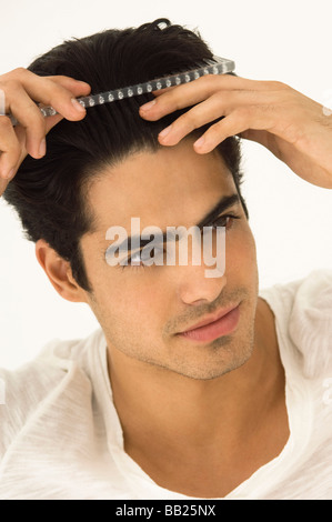 Close-up of a man combing his hair - Stock Photo