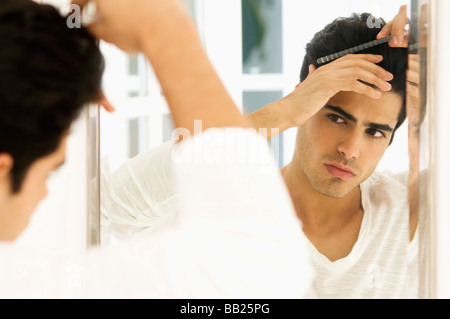 Reflection of a man in the mirror combing his hair - Stock Photo