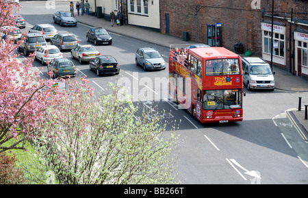 Tourists on an open top sightseeing double decker bus driving through York town centre in England - Stock Photo