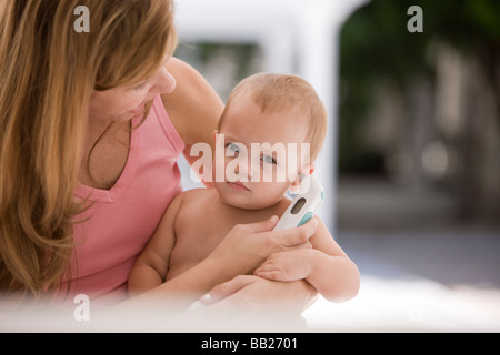 Woman taking her daughter's temperature with a thermometer - Stock Photo